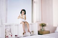 girl sitting on a shelf and playing with toy airplane - stock photo
