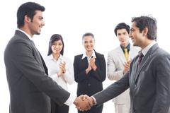 Two businessmen shaking hands with their colleagues applauding Stock Photos