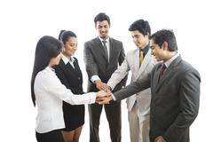 Business executives stacking their hands and smiling Stock Photos