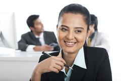 businesswoman smiling in an office with their colleagues in the background - stock photo