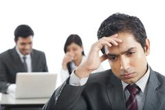 close-up of a businessman looking upset with his colleagues in the background - stock photo