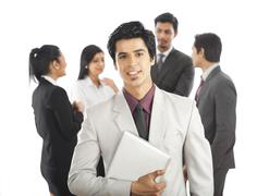 Stock Photo of portrait of a businessman smiling with his colleagues in the background