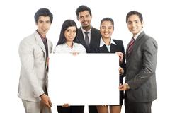 Portrait of business executives holding a placard and smiling Stock Photos