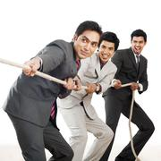 three businessmen playing tug-of-war - stock photo