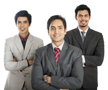 Stock Photo of portrait of three businessmen standing with their arms crossed and smiling