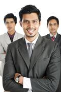 portrait of a businessman smiling with his colleagues in the background - stock photo