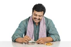 smiling man counting money - stock photo