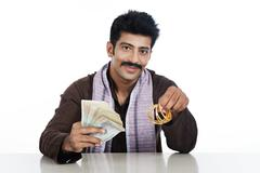 portrait of a man holding money and golden bangles - stock photo
