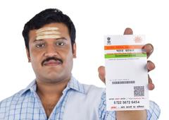 portrait of a south indian man showing an aadhaar card - stock photo