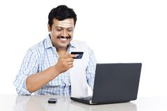 south indian man doing online shopping with a credit card - stock photo