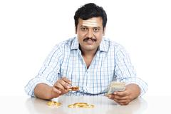 Portrait of a south indian man holding money and gold bangle Stock Photos