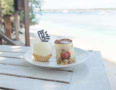 Delicious desserts at beach table Stock Photos