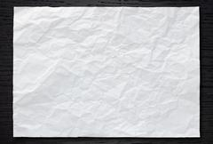 White crumpled paper on dark wood background Stock Photos