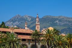 belfry among houses and palms in menton, france. - stock photo