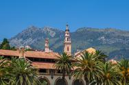 Stock Photo of belfry among houses and palms in menton, france.