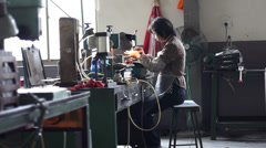Chinese woman operating on drilling machine Stock Footage