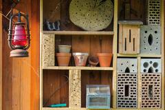 Shelf with insect hotel and garden utensils Stock Photos