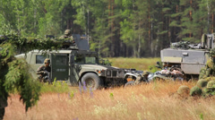 Armoured fighting vehicles and soldiers prepare for attack in the field Stock Footage