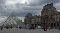 France, Paris, clouds over Louvre and pyramide, people, tourists walking around. Stock Footage