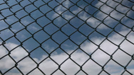 Stock Video Footage of Fast moving clouds behind a chain link fence.
