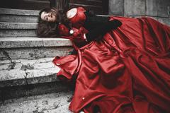 Stock Photo of Lying and bleeding woman in a red Victorian dress
