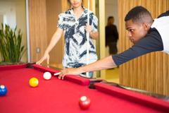 Closeup portrait, young man hanging out, playing billiards at red pool table, Stock Photos