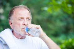 closeup portrait, thirsty senior mature man drinking water outside, isolated  - stock photo