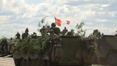 A lot of armoured fighting vehicles with soldiers in the field, camouflage Stock Footage
