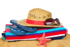 Sunbathing accessories and straw hat on sand Stock Photos