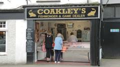 Shoppers buy fish at coakleys fishmonger, mumbles, swansea, wales, uk Stock Footage