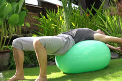 Man stretching on fitness ball, super slow motion, shot at 240fps NTSC Stock Footage