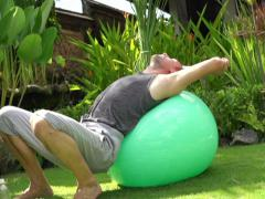 Man stretching, relaxing on fitness ball NTSC Stock Footage