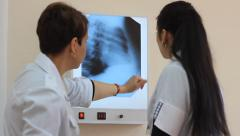 Doctor and laboratory assistant study a radiograph Stock Footage