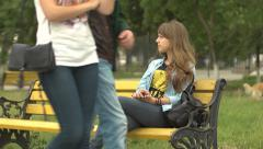 Lonely young girl on a park bench while couples passing by Stock Footage