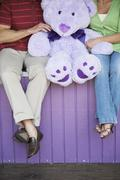 Caucasian couple with teddy bear at theme park Stock Photos