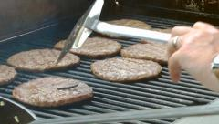 chef cooking barbecue meat oiling and flipping burgers left hand view - stock footage
