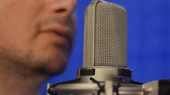 Man speaking into studio microphone. Close-up shot - stock footage