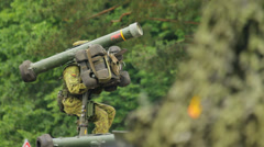 Soldier in camouflage uniform pointing a missile near the trees Stock Footage
