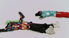 Young girls make snow angels in the snow 4K version Stock Footage