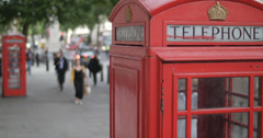 Out of focus tourists between two red phone boxes 4K Stock Footage