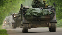 Many armored fighting vehicles drive down the road one after another and pass by Stock Footage