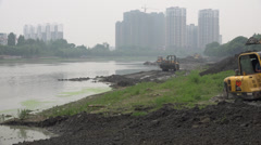 Excavator and bulldozers at work near riverbed in Chengdu, China Stock Footage