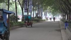 Tuk Tuks driving down sidestreet in Chengdu, China Stock Footage