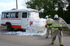 Firefighters  extinguish a burning bus Stock Photos