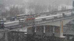 City traffic on bridge on heavy snowy day in Moscow - stock footage