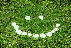 arranging white stone on the green grass in smile concept for eco background - stock photo
