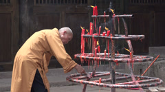 Chinese monk scrapes candle wax off Taoist shrine Stock Footage