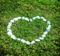 arranging white stone on the green grass in heart concept - stock photo
