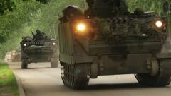 Many soldiers in camouflage uniforms drive in armored fighting vehicles, pass by Stock Footage