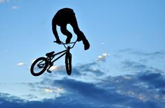 Silhouette of a BMX rider making a bike jump in the air Stock Photos